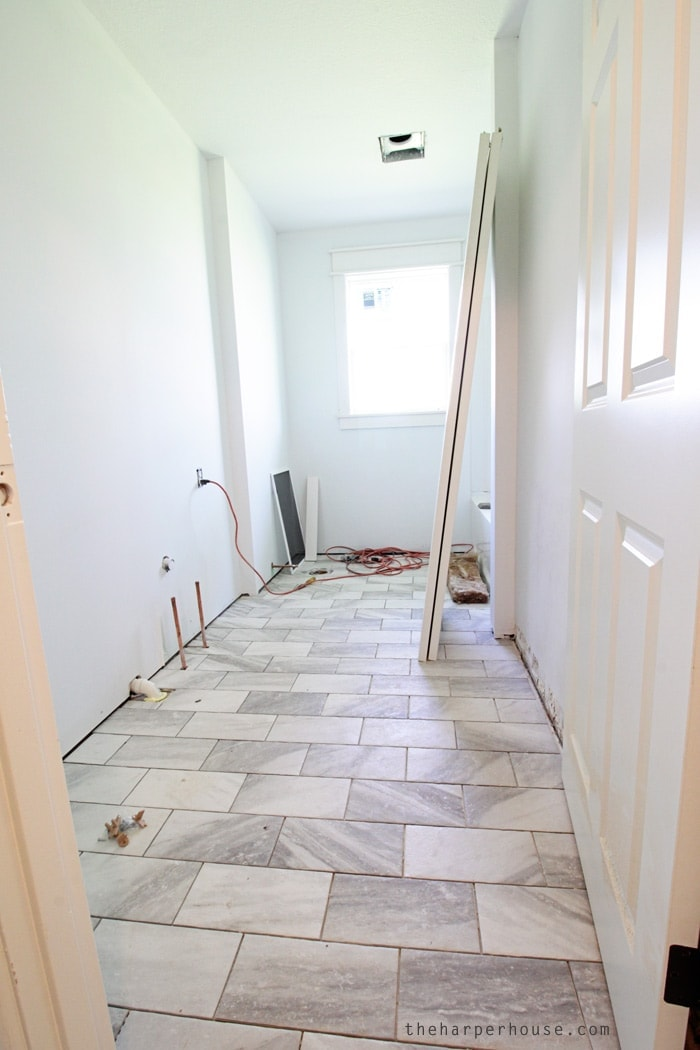 Love these new tile floors in the hall bath at the Flip House, and they're only $2.86/sq ft! Find out where to buy them on the blog! | theharperhouse.com