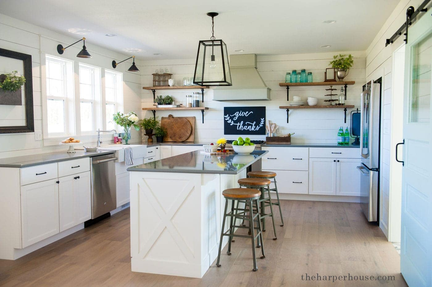 sharing our fixer upper inspired farmhouse kitchen reveal featuring white shaker cabinets, white oak floors, farmhouse sink, open shelves, industrial lighting, & gray quartz countertops| theharperhouse.com