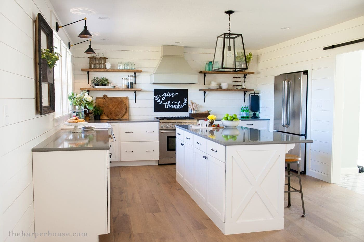 sharing our fixer upper farmhouse kitchen reveal featuring white shaker cabinets, white oak floors, farmhouse sink, open shelves, industrial lighting, & gray quartz countertops| theharperhouse.com