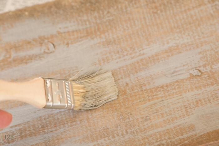 Gray acrylic paint is applied to old barn wood using the dry brush technique.