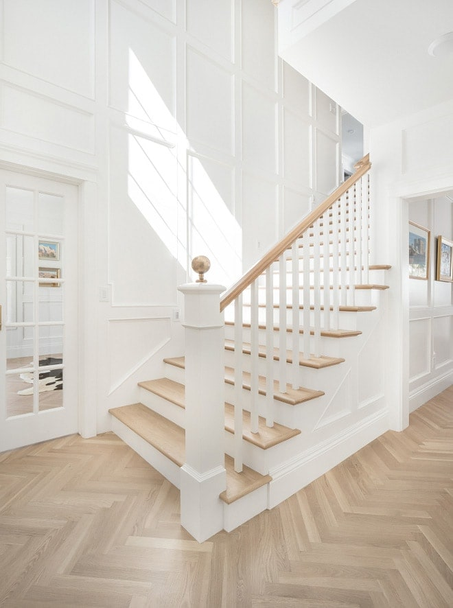 Herringbone wood floors in foyer with white painted trim and millwork designed by The Fox Group