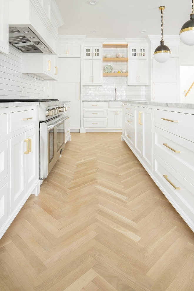 Herringbone wood floors with white shaker kitchen cabinets and gold brass hardware designed by The Fox Group