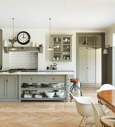 herringbone wood floor with gray shaker kitchen cabinets | design by DeVol Kitchens