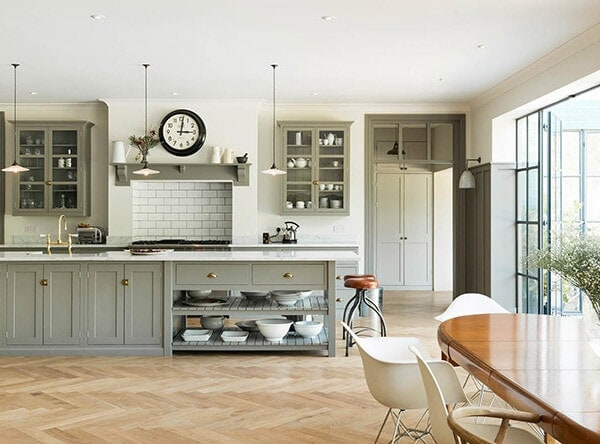 herringbone wood floor with gray shaker kitchen cabinets | design by DeVol Kitchens