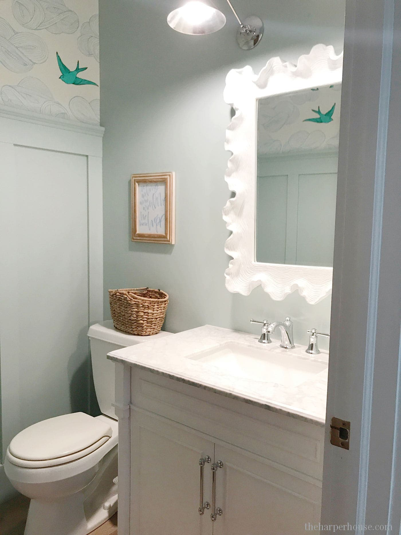 Cool coastal Hamptons style powder bathroom remodel featuring BM Palladian Blue wainscoting and Hygge and West Daydream wallpaper | Bathroom Vanities Single Sink | Bathroom Decorating Ideas | Bathroom Remodeling Ideas | Farmhouse Bathroom | Bathroom Cabinets #bathroomidea #bathroomdesigns #bathroomdecor #bathroomremodel