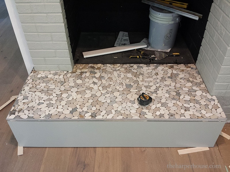 completed tiling job of pebble tile on fireplace hearth