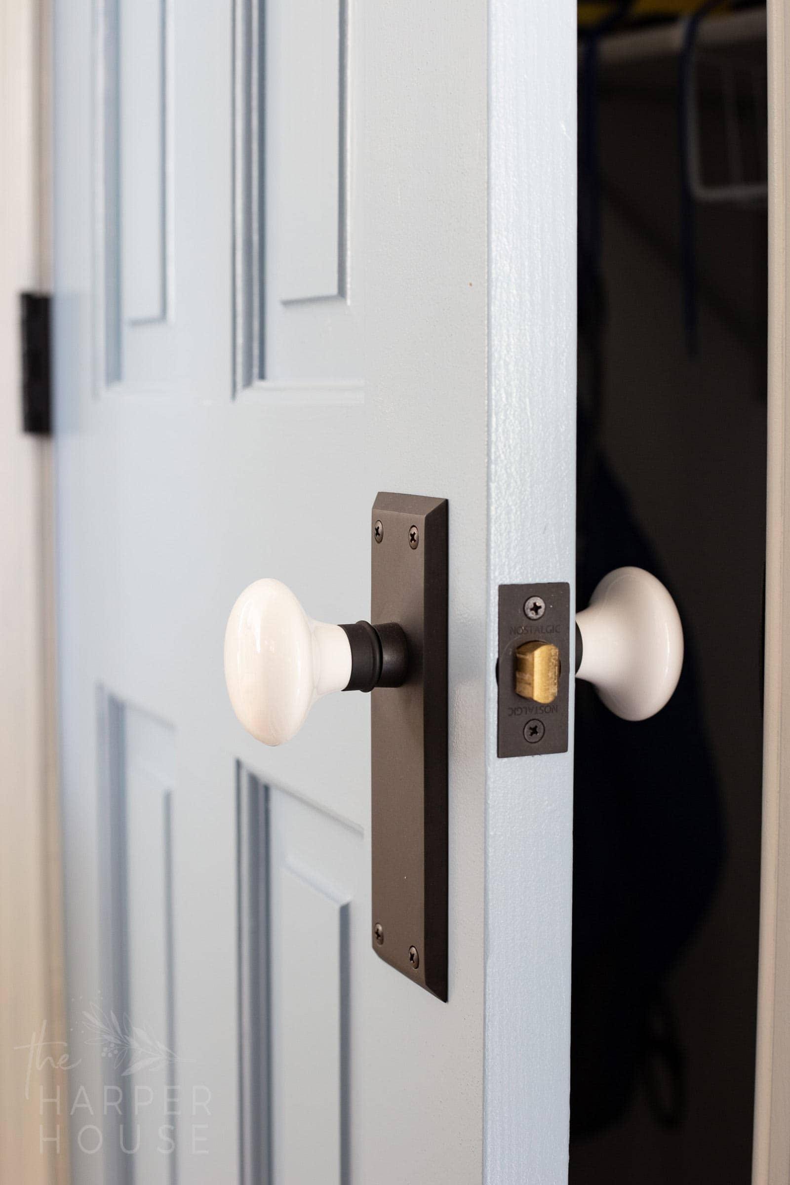 old fashioned porcelain white door knobs on blue door