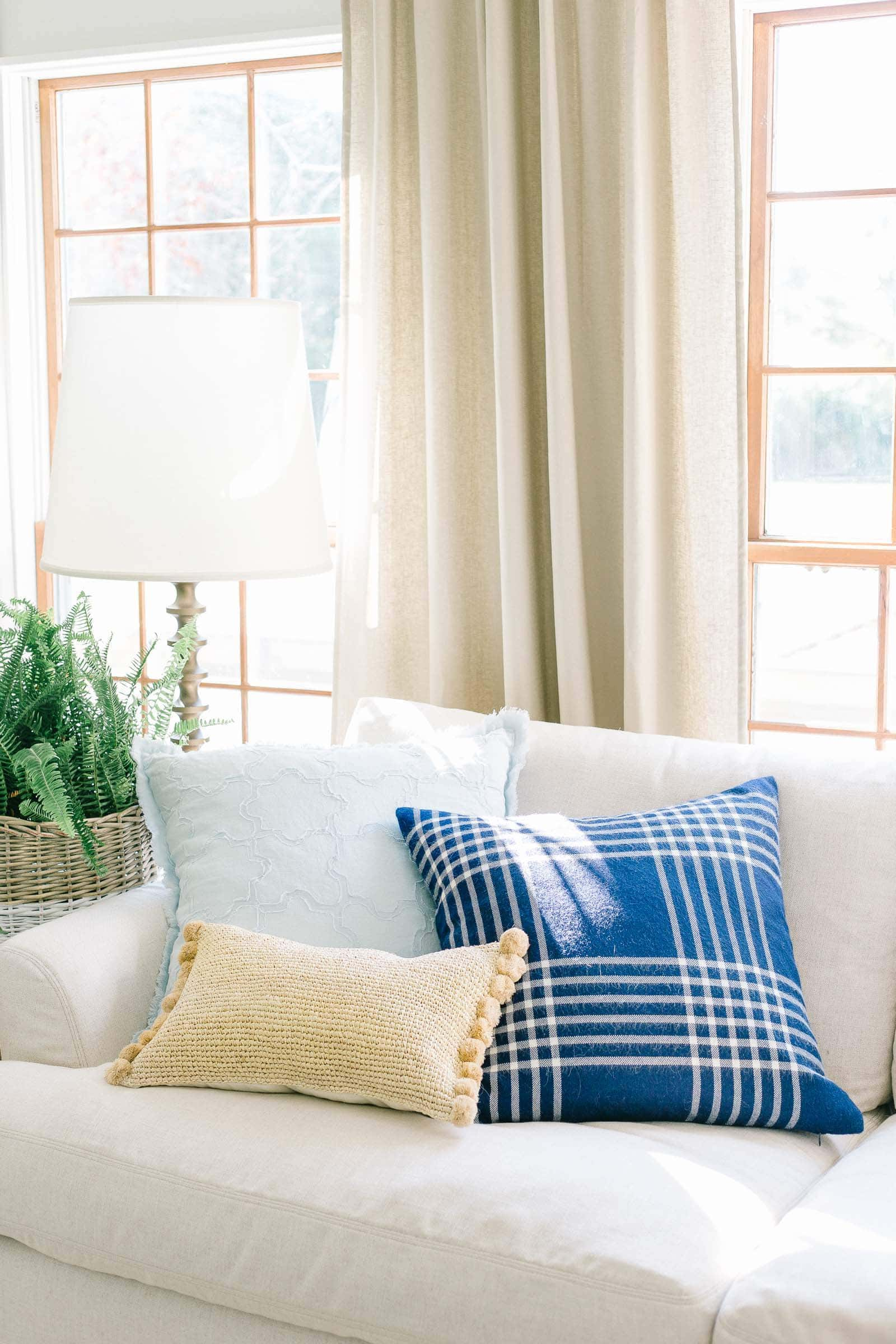 chambray blue pillow and navy blue plaid pillow on sectional sofa