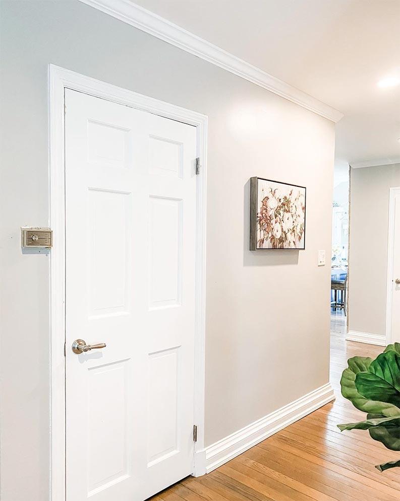 gray hallway walls with white trim and hardwood floors