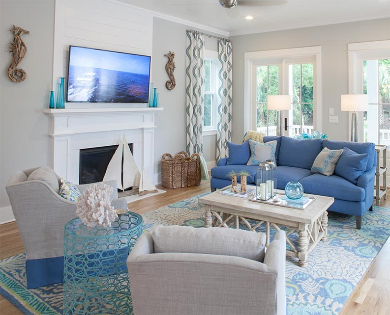 Gray painted living room with blue sofa and white shiplap fireplace